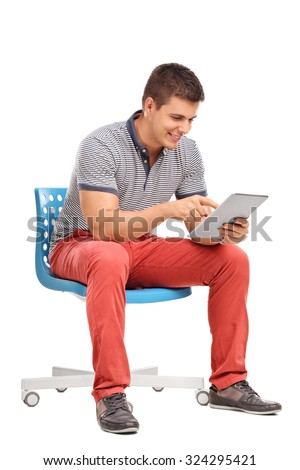 Vertical shot of a young man sitting on a chair and working on a tablet isolated on white background