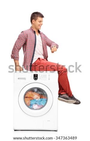 Vertical shot of a young man waiting for the laundry seated on a washing machine isolated on white background