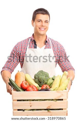 Vertical shot of a young man with a white apron holding a wooden crate full of fresh vegetables and looking at the camera isolated on white background - stock photo