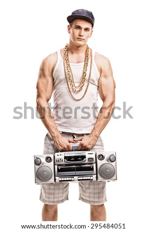 Vertical shot of a young muscular man in hip hop clothes holding a ghetto blaster and looking at the camera isolated on white background - stock photo