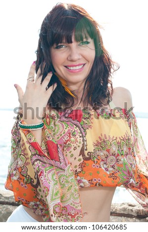 Vertical shot of a young smiling woman posing outdoors - stock photo