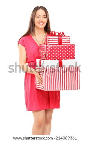 Vertical shot of a young woman holding a bunch of presents isolated on white background