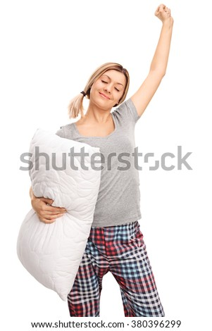 Vertical shot of a young woman in pajamas holding a pillow and stretching herself isolated on white background - stock photo