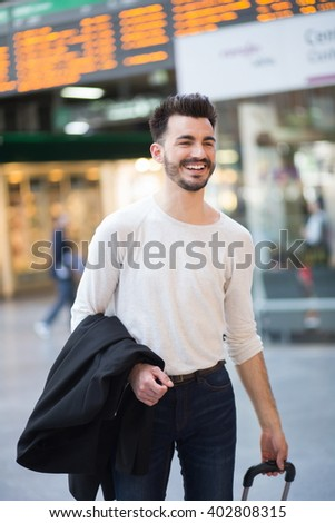 Vertical shot of an attractive smiley casual young man, carrying a suitcase at a train station lobby