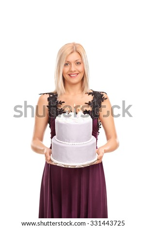 Vertical shot of an elegant woman in a purple dress carrying a birthday cake with lit candles on it isolated on white background - stock photo