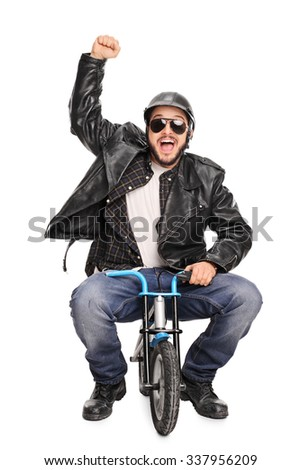 Vertical shot of an excited male motorcyclist riding a tiny bicycle and gesturing happiness isolated on white background - stock photo