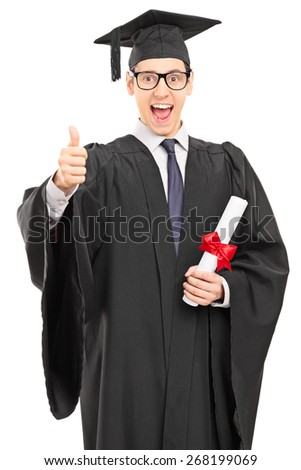 Vertical shot of an overjoyed graduate student in a graduation gown, holding a diploma and giving a thumb up isolated on white background - stock photo