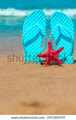 Vertical shot of beach shoes and starfish on the sea - stock photo