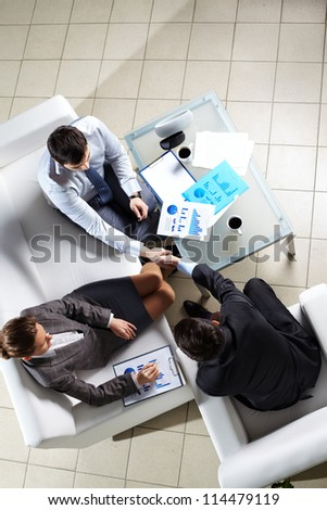 Vertical shot of business people shaking hands - stock photo