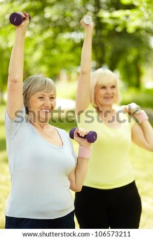 Vertical shot of elderly women doing exercises with dumbbells - stock photo