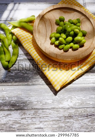 Vertical shot of green soybeans on a wooden plate below the sunlight rays - stock photo