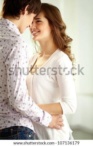 Vertical shot of happy sweethearts looking at one another - stock photo