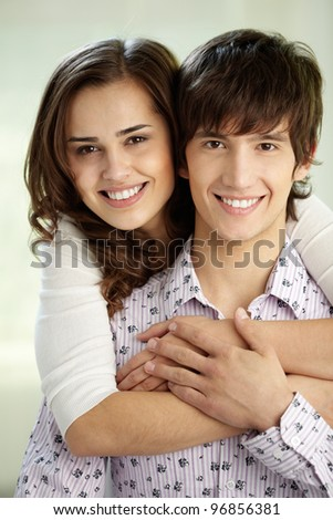 Vertical shot of happy sweethearts smiling at camera - stock photo