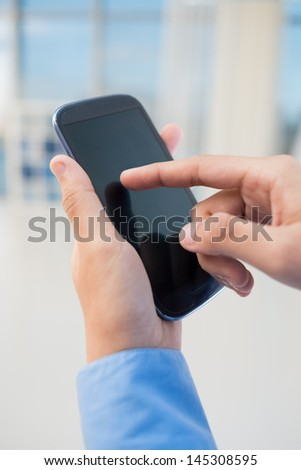Vertical shot of human hands touching a smartphone  - stock photo