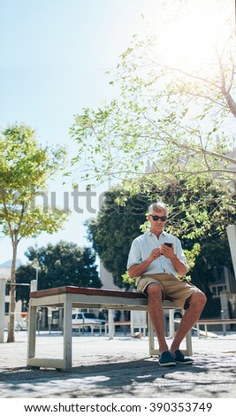 Vertical shot of mature man sitting outdoor on a bench and using mobile phone. Tourist relaxing on a bench in city and looking for directions on his mobile phone. - stock photo