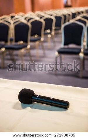 Vertical shot of microphone and chairs in auditorium - stock photo