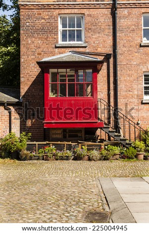 Vertical shot of  old courtyard with redbrick house and iron steps leading to a red porch - stock photo