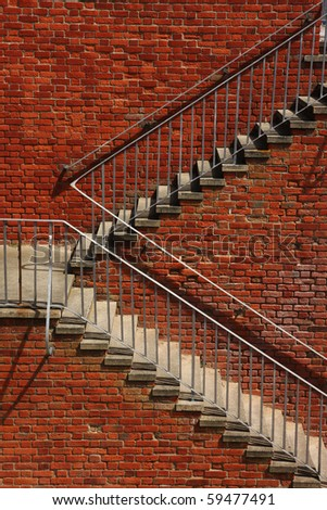 Vertical shot of outside steps against a brick wall, taken in sunshine. - stock photo