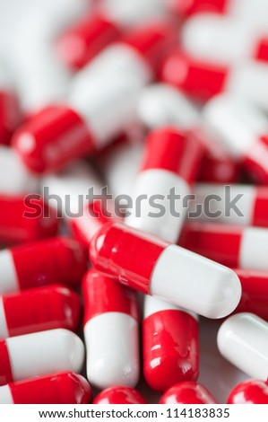 Vertical shot of red and white capsules, close-up - stock photo