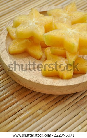 Vertical shot of starfruit on a wooden plate - stock photo