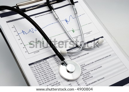 Vertical shot of Stethoscope on clipboard over blood pressure graph printout and table of results - stock photo