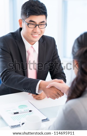 Vertical shot of two business partners shaking hands with satisfaction - stock photo