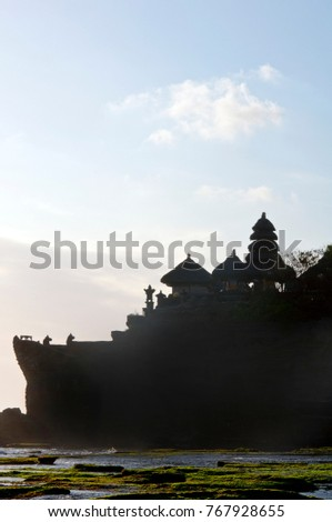 Vertical silhouette image of Pura Tanah Lot at sunset, famous hindu temple in South of Bali, Indonesia