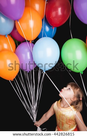 Vertical studio portrait of positive Caucasian blond little girl with colorful balloons - stock photo