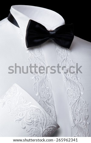 Vertical studio shot of a formal white shirt with fancywork and a black bowtie on black background - stock photo