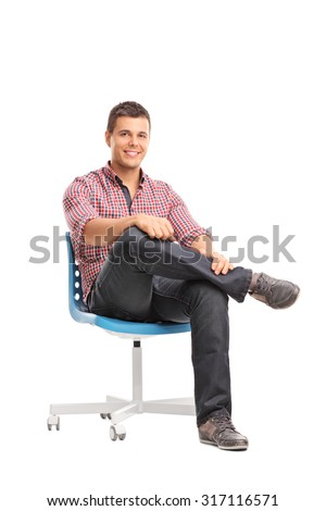 Vertical studio shot of a relaxed young man sitting on a chair and looking at the camera isolated on white background - stock photo
