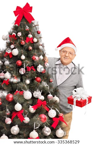 Vertical studio shot of a senior man with Santa hat standing behind a Christmas tree and holding a present wrapped in red paper isolated on white background - stock photo