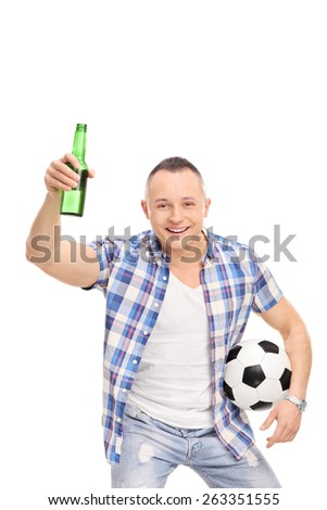 Vertical studio shot of a young man holding a football and a beer bottle and cheering isolated on white background - stock photo