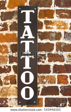 Vertical tattoo sign on a brick wall - stock photo
