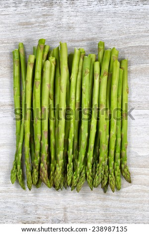 Vertical top view of a pile of asparagus on rustic white wood  - stock photo