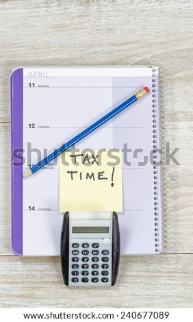 Vertical top view of an office wooden desktop with small calendar, calculator and sharpen blue pencil with reminder of doing Tax Return.  - stock photo