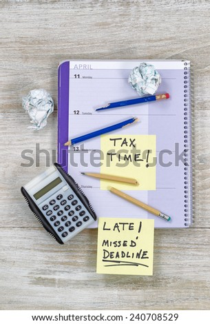 Vertical top view of an office wooden desktop with small calendar, calculator, wadded paper, and broken pencils, showing teeth marks, during tax preparation.   - stock photo