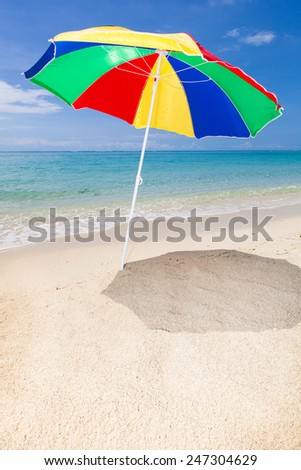 vertical travel background with a colorful sunshade, beach turquoise sea and blue sky, Le Morne, Mauritius, Africa  - stock photo