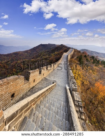 Vertical view down on bricks ladder atop of The Great Wall of China high in Mutianyu mountains with nobody walking along the wall pathway - stock photo