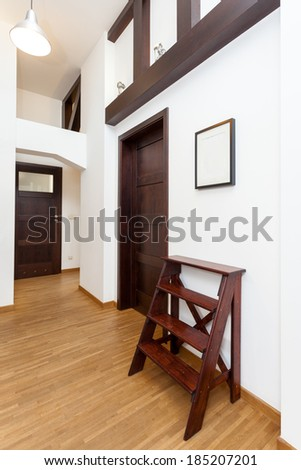 Vertical view of a corridor with brown decorative ladder - stock photo