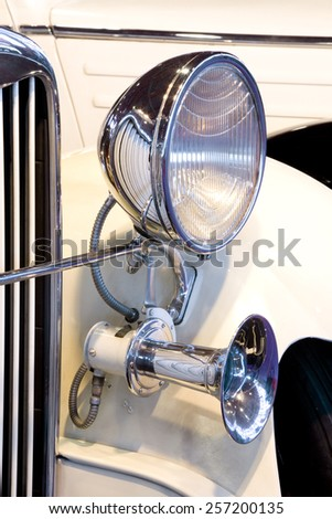 Vertical view of a luxury old yellow car detail. Old Car Headlight.   - stock photo