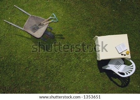 Vertical view of a wheelbarrow, with garden tools, and a garden table with book, sunglasses and drink, all on a green lawn. Space for text on the green of the grass.