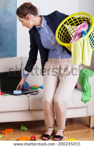 Vertical view of a young businesswoman doing the housework - stock photo