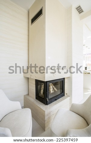 Vertical view of beige fireplace in elegant home - stock photo