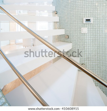 Vertical view of granitic stairs with golden rails - stock photo