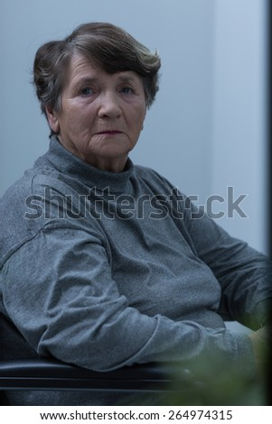 Vertical view of lonely disabled female pensioner - stock photo
