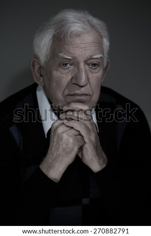 Vertical view of low-spirited older man sitting alone - stock photo