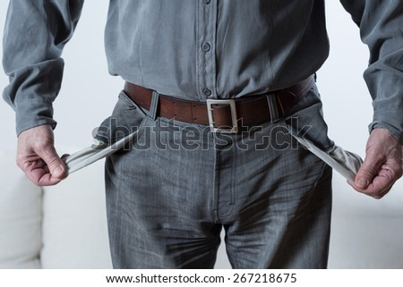 Vertical view of man showing empty pockets - stock photo