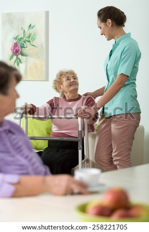 Vertical view of nurse helping disabled woman - stock photo