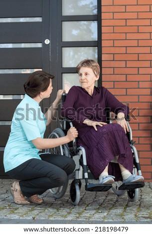 Vertical view of nurse talking with senior woman on wheelchair - stock photo