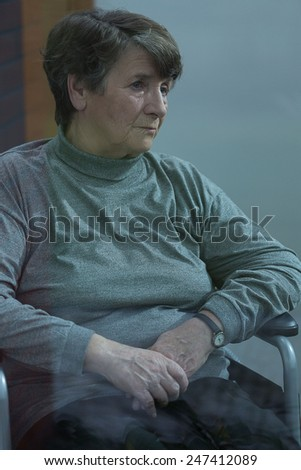 Vertical view of older melancholic woman sitting alone - stock photo